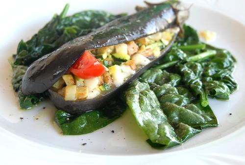 Melanzane ripiene con verdure e formaggio su spinaci spadellati.